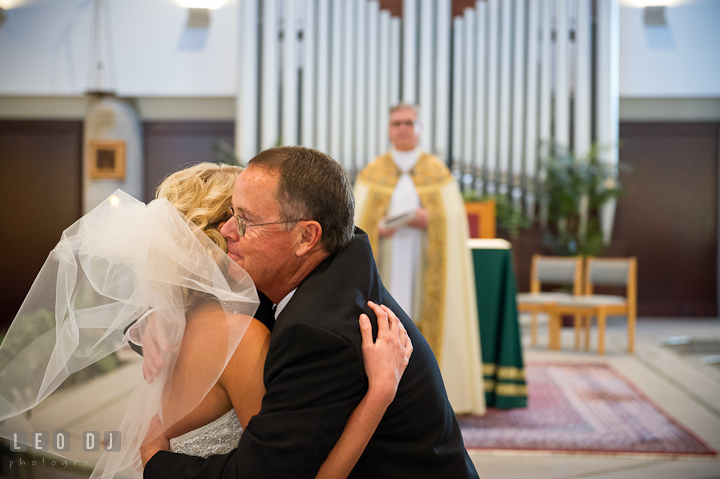 Father of Bride hugging daughter during giving away. Ceremony wedding photos at Sacred Heart Church, Glyndon, Maryland by photographers of Leo Dj Photography. http://leodjphoto.com