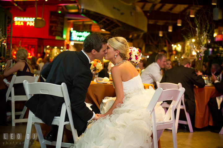 Bride and Groom kissing by the sweet heart table. Baltimore Museum of Industry wedding photos by photographers of Leo Dj Photography. http://leodjphoto.com