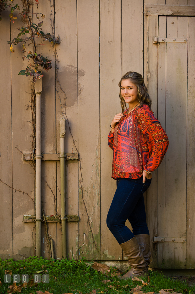 Girl in red blouse standing and posing by a brown barn. Eastern Shore, Maryland, Queen Anne's County High School senior portrait session by photographer Leo Dj Photography. http://leodjphoto.com
