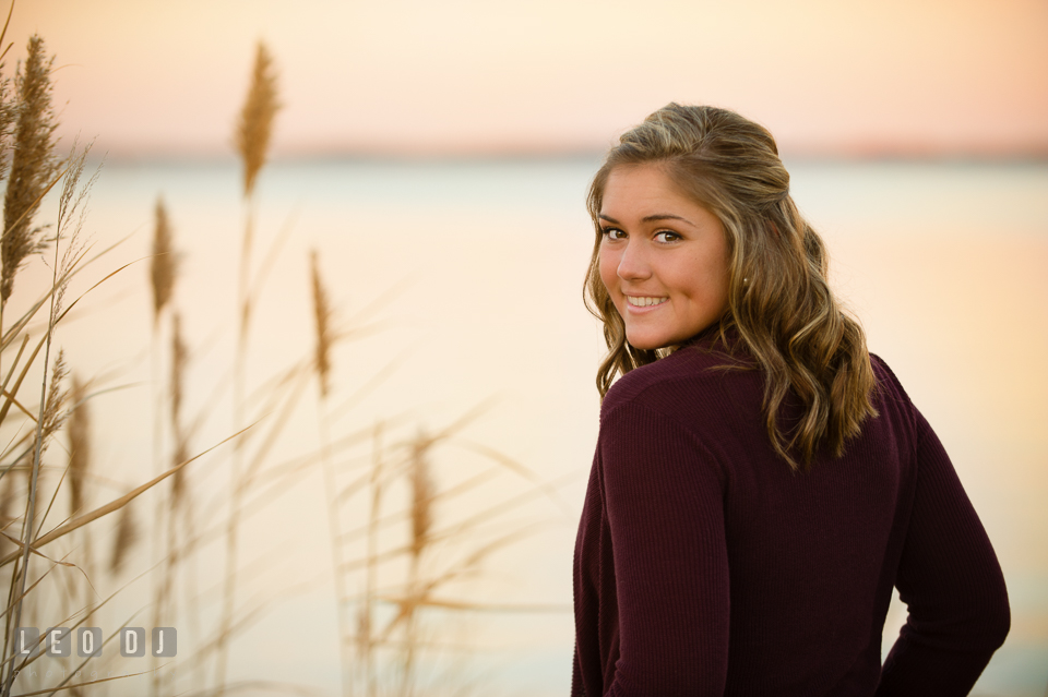 Girl looking walking on the beach looking back. Eastern Shore, Maryland, Queen Anne's County High School senior portrait session by photographer Leo Dj Photography. http://leodjphoto.com