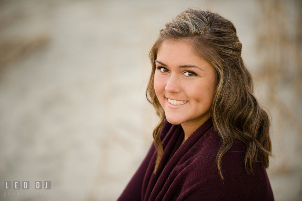 Close up photo of girl sitting on the beach smiling with dimples. Eastern Shore, Maryland, Queen Anne's County High School senior portrait session by photographer Leo Dj Photography. http://leodjphoto.com