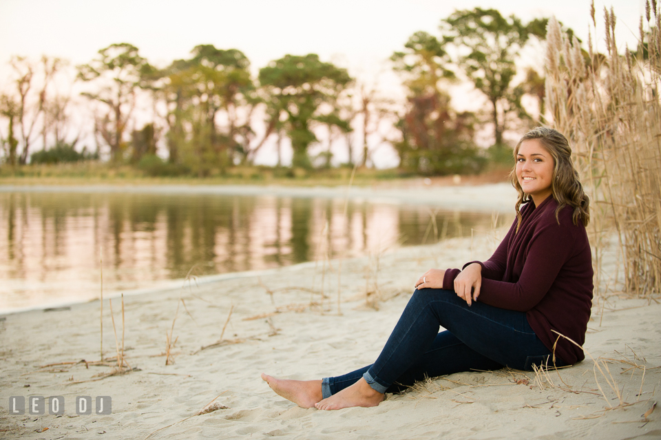 Girl in jeans and burgundy outfit lounging on the beach. Eastern Shore, Maryland, Queen Anne's County High School senior portrait session by photographer Leo Dj Photography. http://leodjphoto.com