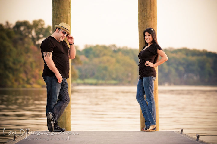 Engaged couple posing by the pier. Guy with sunglasses and hat. Eastern Shore MD engagement pre-wedding photo session pier boat tattoo