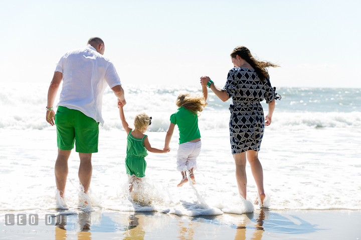 Family holding hands and jumping over the water waves on the beach. Ocean City, Maryland Eastern Shore candid children and family lifestyle photo session by photographers of Leo Dj Photography. http://leodjphoto.com