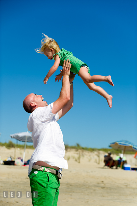 Father playing with his daughter lift her up in the air. Ocean City, Maryland Eastern Shore candid children and family lifestyle photo session by photographers of Leo Dj Photography. http://leodjphoto.com