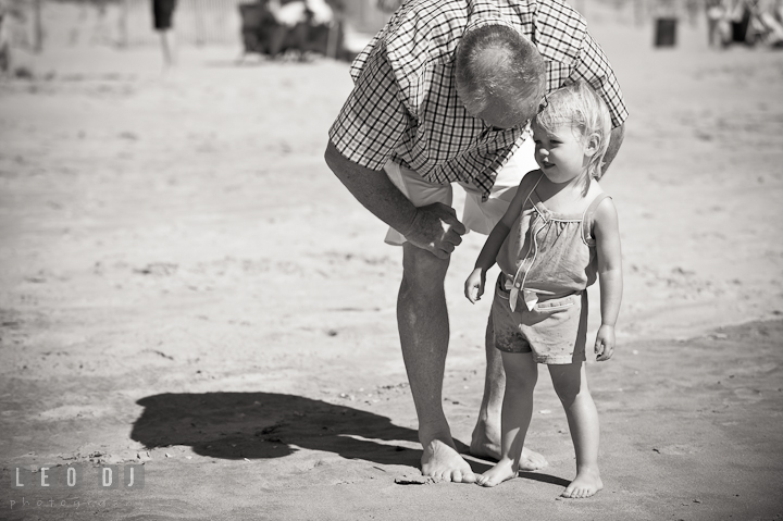 Grandfather talking to his granddaughter. Ocean City, Maryland Eastern Shore candid children and family lifestyle photo session by photographers of Leo Dj Photography. http://leodjphoto.com