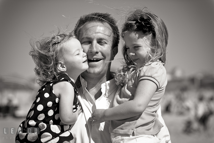 Father picking up his two girls and cuddling. Ocean City, Maryland Eastern Shore candid children and family lifestyle photo session by photographers of Leo Dj Photography. http://leodjphoto.com