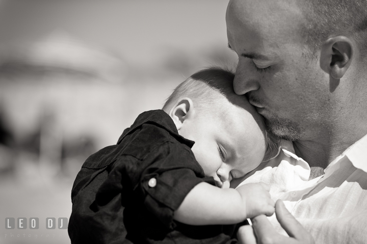 Father kissing his baby boy. Ocean City, Maryland Eastern Shore candid children and family lifestyle photo session by photographers of Leo Dj Photography. http://leodjphoto.com