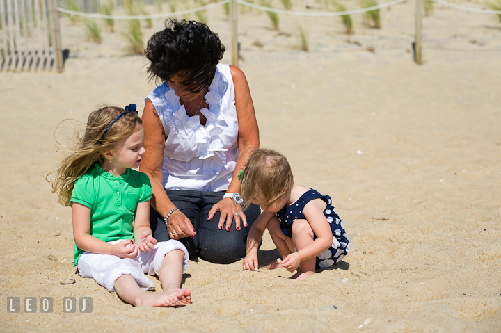 Two toddler girls playing with their Grandmother on the beach sand. Ocean City, Maryland Eastern Shore candid children and family lifestyle photo session by photographers of Leo Dj Photography. http://leodjphoto.com