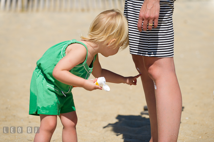 Little girl applying sun screen on Mommy's legs. Ocean City, Maryland Eastern Shore candid children and family lifestyle photo session by photographers of Leo Dj Photography. http://leodjphoto.com