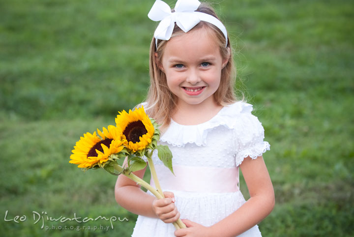 Girl holding sunflowers. Edgewater, Annapolis, Eastern Shore Maryland fun and candid children and family lifestyle photo session by photographers of Leo Dj Photography.