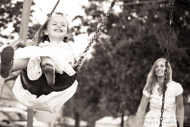 Girl giggling in a swing. Edgewater, Annapolis, Eastern Shore Maryland fun and candid children and family lifestyle photo session by photographers of Leo Dj Photography.