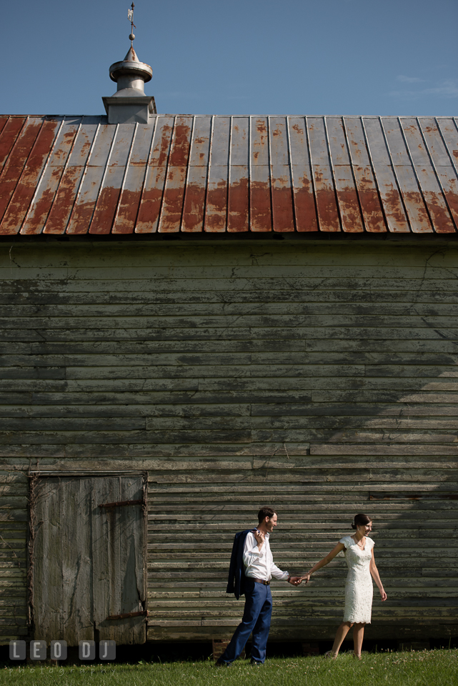 Bride and Groom walking together by the barn. The Oaks Waterfront Inn wedding, St Michaels, Eastern Shore, Maryland, by wedding photographers of Leo Dj Photography. http://leodjphoto.com