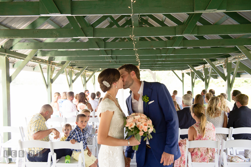 Bride and Groom kissing at the end of the aisle after the ceremony. The Oaks Waterfront Inn wedding, St Michaels, Eastern Shore, Maryland, by wedding photographers of Leo Dj Photography. http://leodjphoto.com