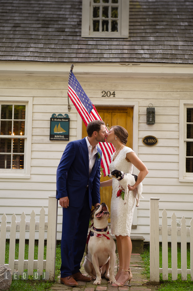 Bride and Groom kissing in front of their cottage with their dogs looking. The Oaks Waterfront Inn wedding, St Michaels, Eastern Shore, Maryland, by wedding photographers of Leo Dj Photography. http://leodjphoto.com