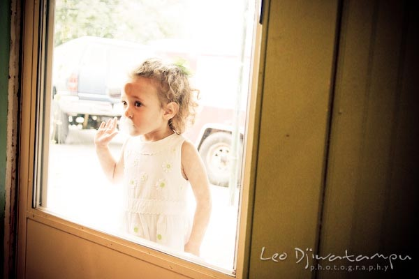 girl looking through door glass window. Children family reunion birthday photography Tilghman Island Annapolis Kent Island Eastern Shore MD
