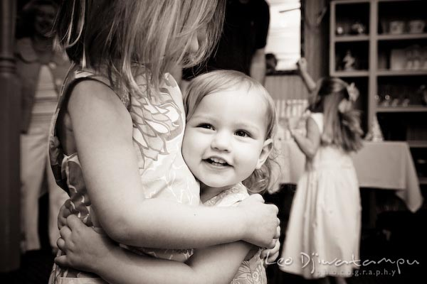 girl hugging her baby sister. Children family reunion birthday photography Tilghman Island Annapolis Kent Island Eastern Shore MD