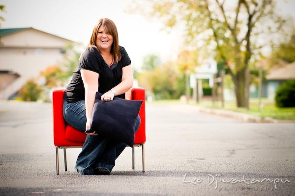 Girl on red chair posing with black pillow, laughing. Commercial work photography Annapolis Eastern Shore MD Washington DC