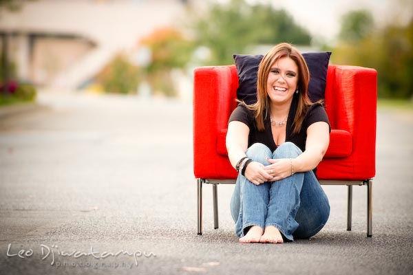 Girl sitting on ground posing in front of red chair, laughing. Commercial work photography Annapolis Eastern Shore MD Washington DC