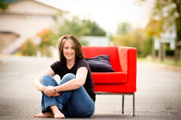 Girl with hair highlight, sitting on ground by red chair, smiling. Commercial work photography Annapolis Eastern Shore MD Washington DC