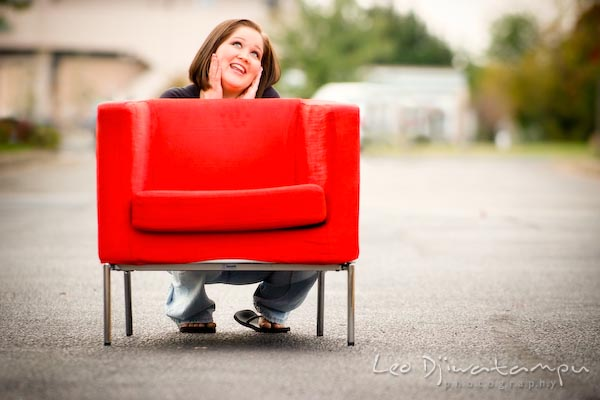 Girl squatting on ground behind red chair, posing, smiling. Commercial work photography Annapolis Eastern Shore MD Washington DC