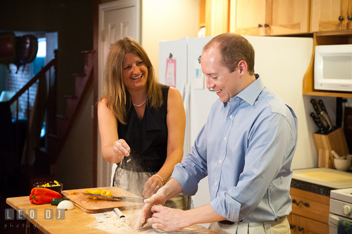 Engaged couple throwing flour at each other while cooking. Engagement photo session at town home near Federal Hill Baltimore Maryland by wedding photographers of Leo Dj Photography (http://leodjphoto.com)