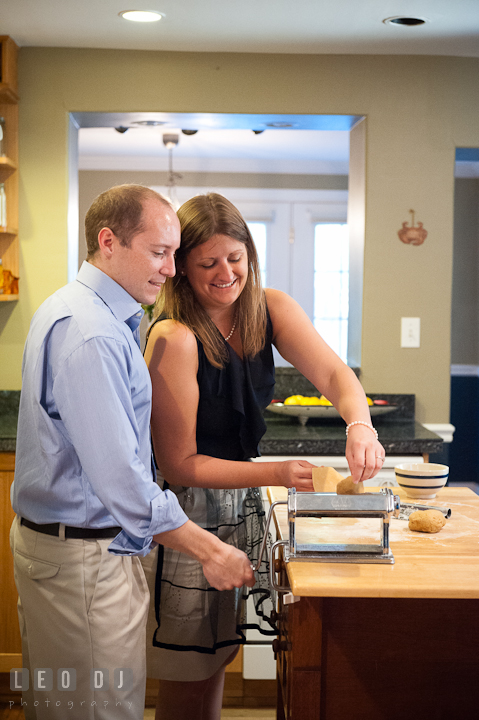 Engaged couple cooking put pasta dough in roller. Engagement photo session at town home near Federal Hill Baltimore Maryland by wedding photographers of Leo Dj Photography (http://leodjphoto.com)