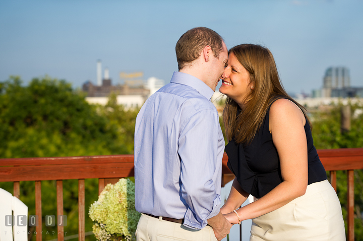 Engaged couple holding hands and touching noses on their rooftop deck. Engagement photo session at town home near Federal Hill Baltimore Maryland by wedding photographers of Leo Dj Photography (http://leodjphoto.com)