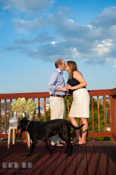 Engaged girl kissing with her fiancé at rooftop deck. Engagement photo session at town home near Federal Hill Baltimore Maryland by wedding photographers of Leo Dj Photography (http://leodjphoto.com)