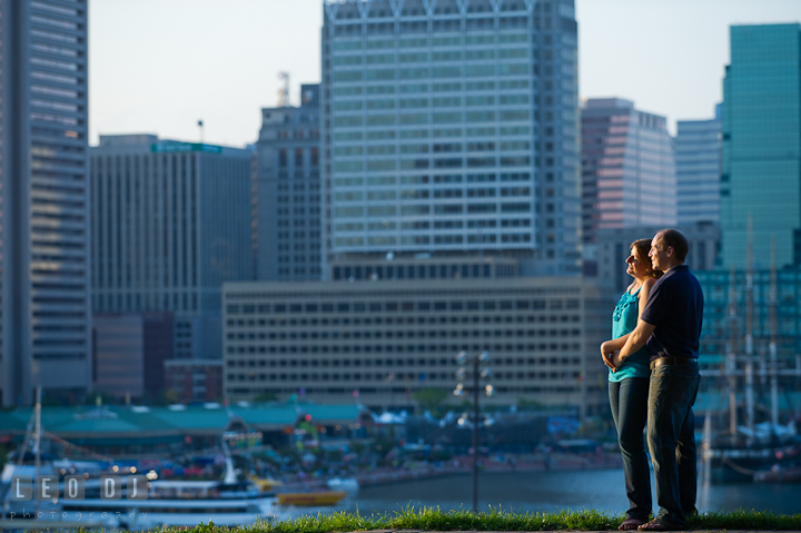 Engaged couple cuddling and enjoying the view of skyscrapers at Baltimore downtown inner harbor. Engagement photo session at town home near Federal Hill Park Baltimore Maryland by wedding photographers of Leo Dj Photography (http://leodjphoto.com)