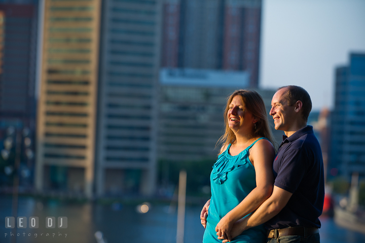Engaged guy cuddling with his fiancée, laughing, and enjoying the view of Baltimore inner harbor. Engagement photo session at town home near Federal Hill Park Baltimore Maryland by wedding photographers of Leo Dj Photography (http://leodjphoto.com)