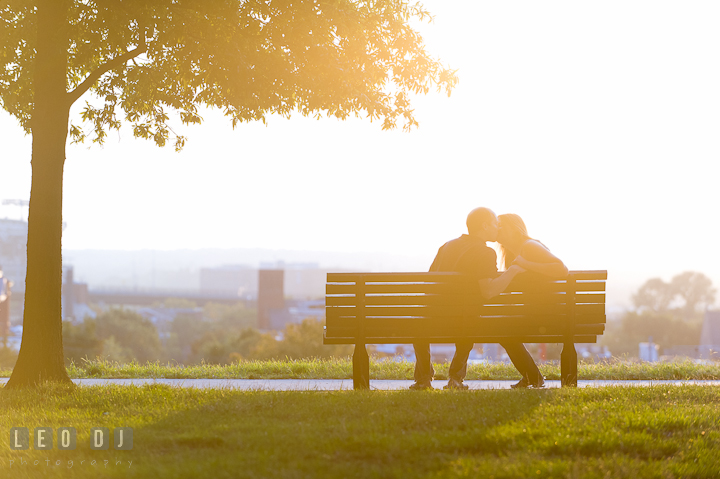 Engaged couple sitting on the bench beneath a tree, kissing. Engagement photo session at town home near Federal Hill Park Baltimore Maryland by wedding photographers of Leo Dj Photography (http://leodjphoto.com)
