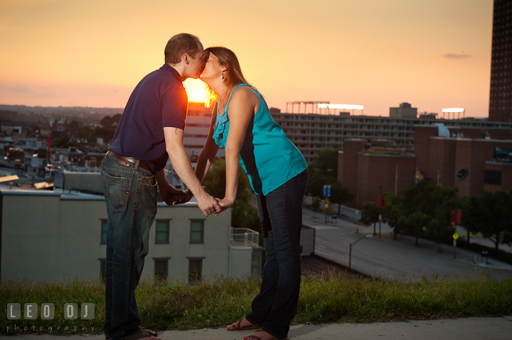 Engaged couple holding hands and kissing during a sunset. Engagement photo session at town home near Federal Hill Park Baltimore Maryland by wedding photographers of Leo Dj Photography (http://leodjphoto.com)