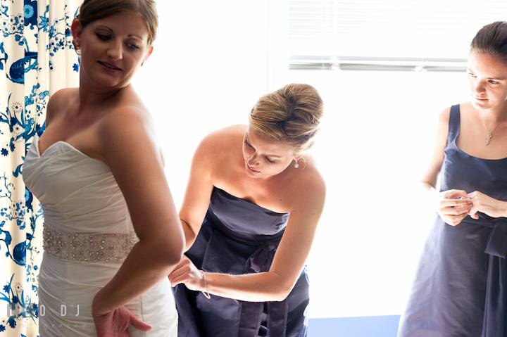 Maid of honor helping Bride buttoning the wedding dress. Getting ready and ceremony wedding photos at private estate at Preston, Easton, Eastern Shore, Maryland by photographers of Leo Dj Photography. http://leodjphoto.com