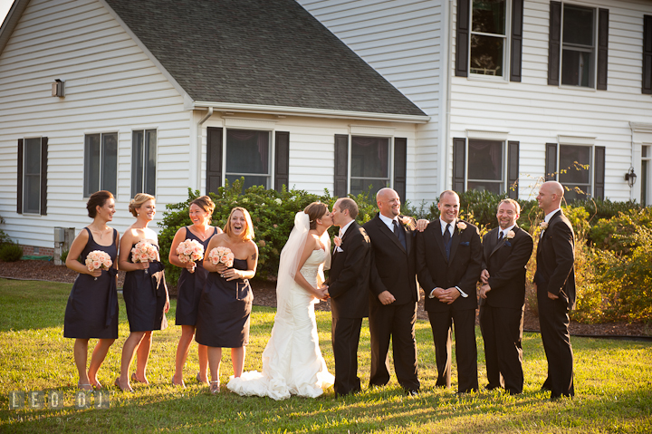 Bride and Groom kissing while posing with wedding party. Reception party wedding photos at private estate at Preston, Easton, Eastern Shore, Maryland by photographers of Leo Dj Photography. http://leodjphoto.com
