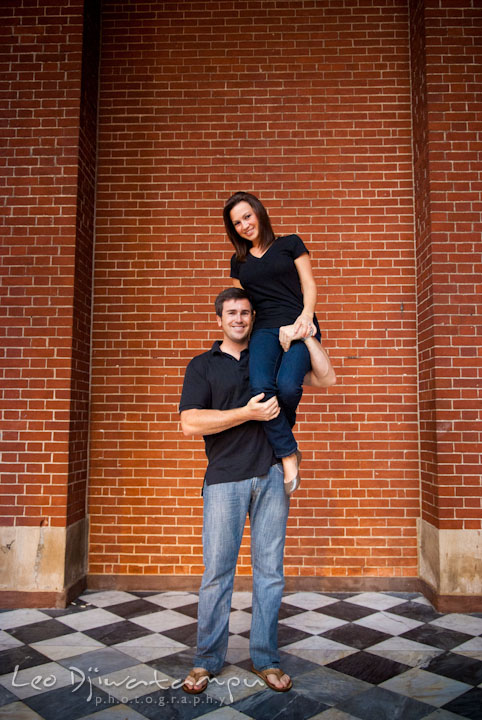 Engaged girl sits on her fiancé's shoulder and arm. Tremont Plaza Hotel and Grand Historic Venue Baltimore Pre-wedding Engagement Photo Session by wedding photographers Leo Dj Photography