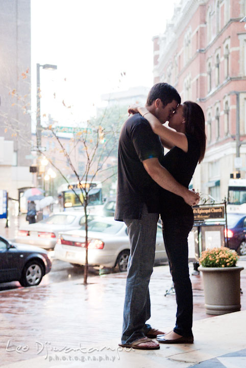 Engaged couple embracing and kissing with the city in the background