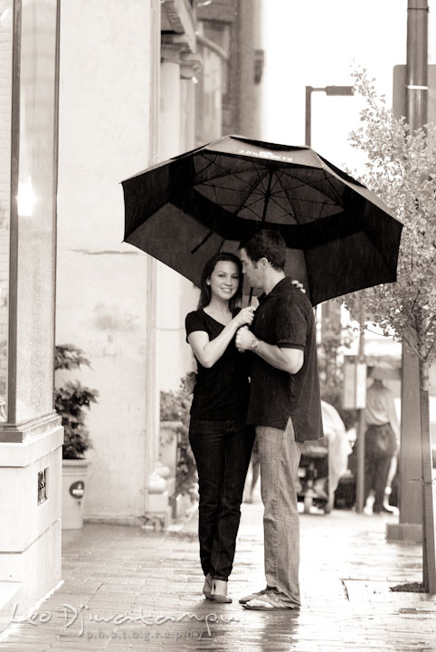 Engaged girl smiling with her fiancé under the rain and umbrella. Tremont Plaza Hotel and Grand Historic Venue Baltimore Pre-wedding Engagement Photo Session by wedding photographers Leo Dj Photography