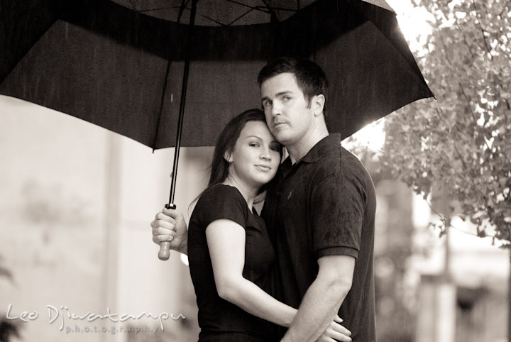 Engaged couple cuddling under the rain and umbrella. Tremont Plaza Hotel and Grand Historic Venue Baltimore Pre-wedding Engagement Photo Session by wedding photographers Leo Dj Photography