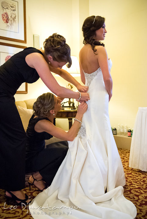 Bridesmaid and maid of honor help bride buttoning up bride's dress. Baltimore Maryland Tremont Plaza Hotel Grand Historic Venue wedding ceremony and reception photos, by photographers of Leo Dj Photography.