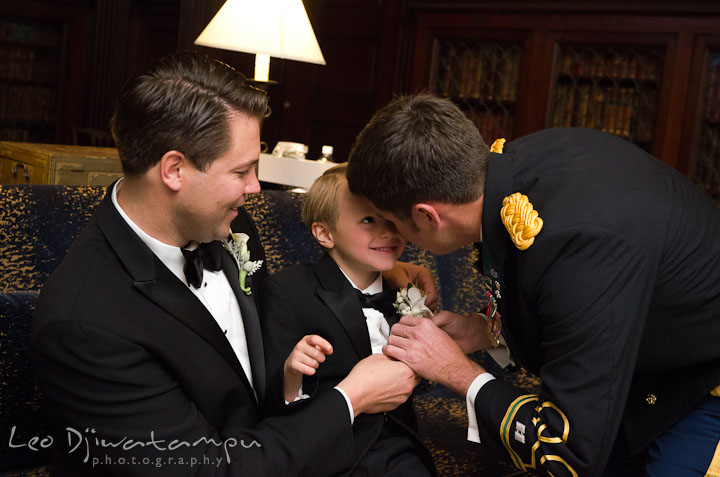 Groom help ringbearer put on boutonniere. Baltimore Maryland Tremont Plaza Hotel Grand Historic Venue wedding ceremony and reception photos, by photographers of Leo Dj Photography.