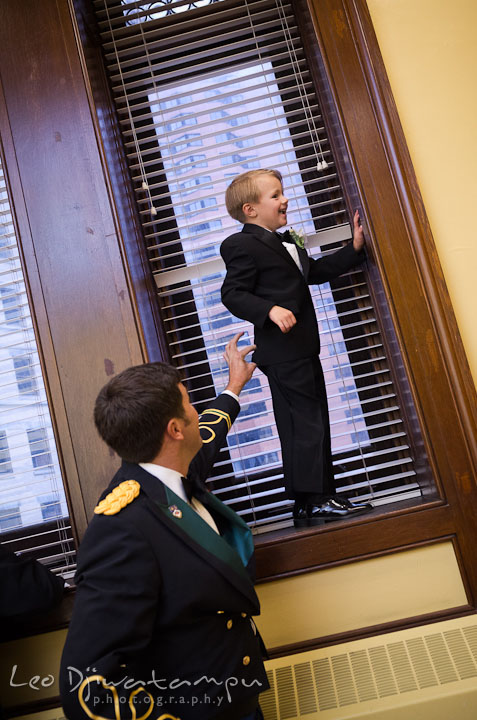 Groom guarding ringbearer not to fall from window. Baltimore Maryland Tremont Plaza Hotel Grand Historic Venue wedding ceremony and reception photos, by photographers of Leo Dj Photography.