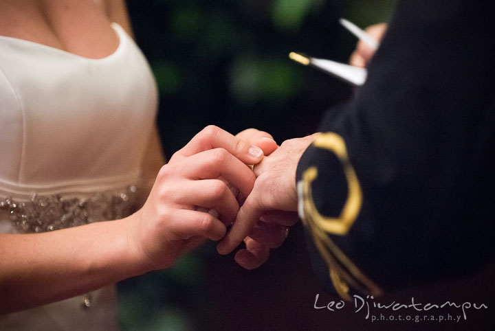 Bride sliding wedding band to Groom's finger. Baltimore Maryland Tremont Plaza Hotel Grand Historic Venue wedding ceremony and reception photos, by photographers of Leo Dj Photography.