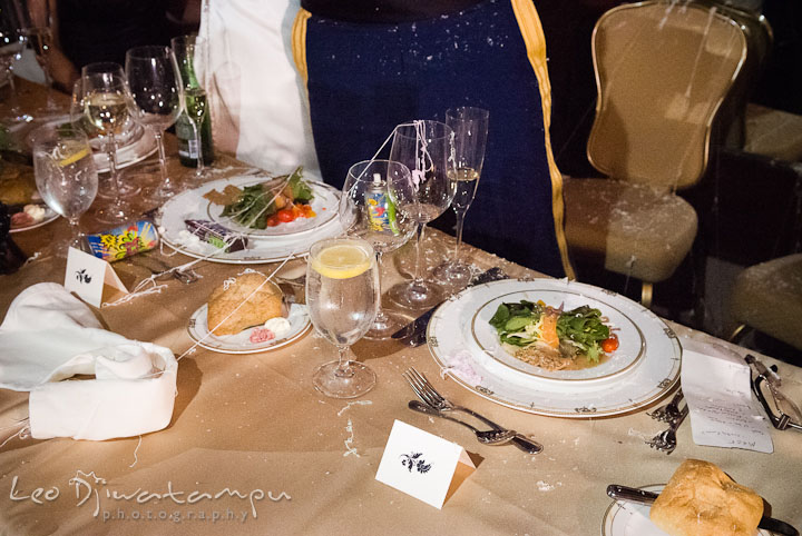 Mess on the table and dinner plates after the silly string prank. Baltimore Maryland Tremont Plaza Hotel Grand Historic Venue wedding ceremony and reception photos, by photographers of Leo Dj Photography.