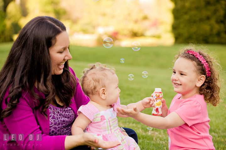 Mom, girl and baby sister playing bubbles. Washington DC, Silver Spring, Maryland candid children and family lifestyle photo session by photographers of Leo Dj Photography.