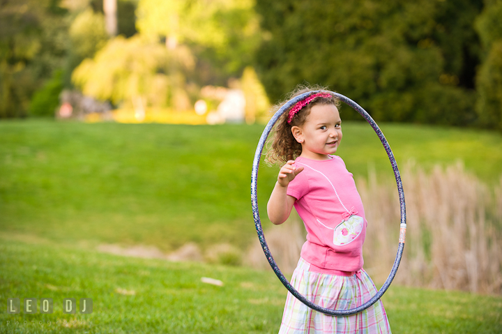 Cute girl putting hula hoop on her head. Washington DC, Silver Spring, Maryland candid children and family lifestyle photo session by photographers of Leo Dj Photography.