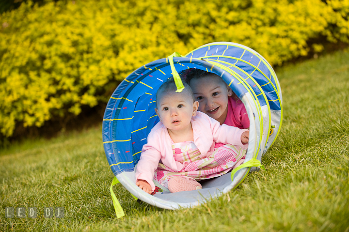 Baby girl and her sister crawling through tube. Washington DC, Silver Spring, Maryland candid children and family lifestyle photo session by photographers of Leo Dj Photography.