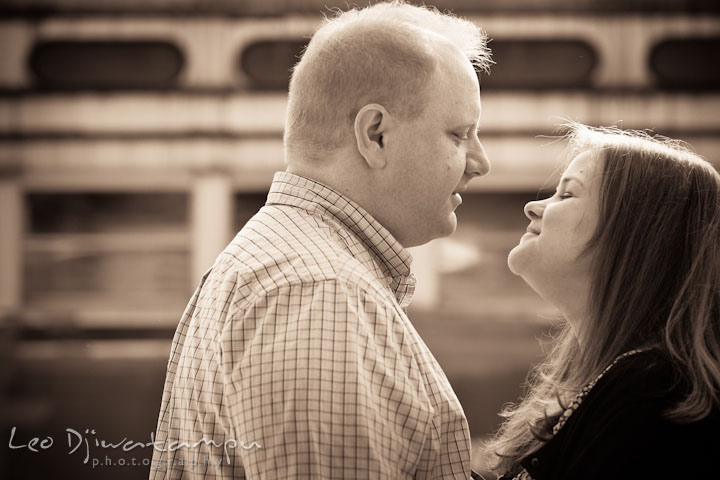 Engaged guy looking at his fiancée. Pre wedding engagement photo session at Glen Echo Park Maryland by wedding photographer Leo Dj Photography