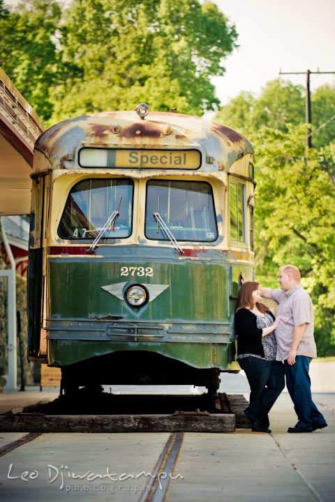 Engaged couple talking to each other by an old trolley or tram. Pre wedding engagement photo session at Glen Echo Park Maryland by wedding photographer Leo Dj Photography
