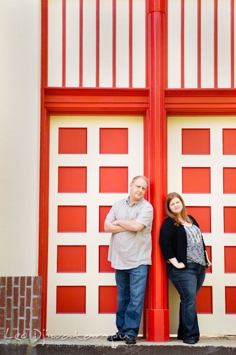 Engaged girl and her fiancé posing by a red doors. Pre wedding engagement photo session at Glen Echo Park Maryland by wedding photographer Leo Dj Photography